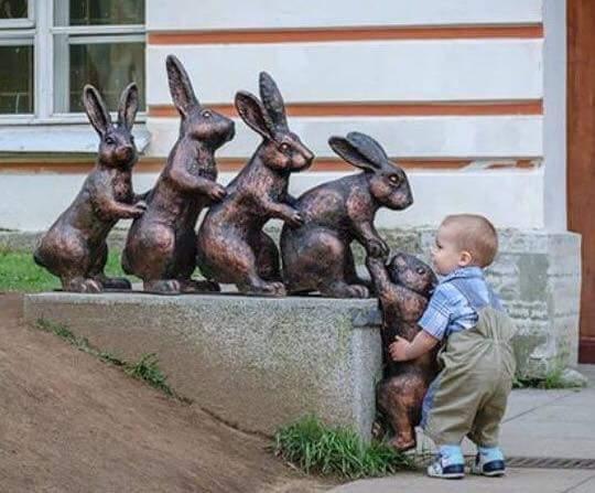 Bebé trata de ayudar a un conejo de piedra (estatua de varios conejos en fila) - Empatía infantil